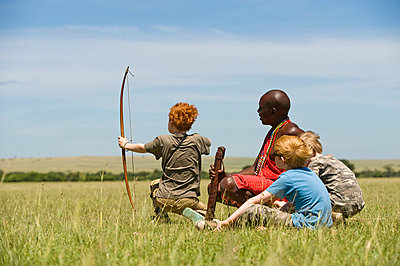 Safari guide, Salaash Ole Morompi, teaches children archery Maasai style - p6521201 by John Warburton-Lee