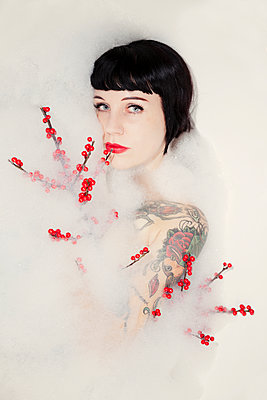 Woman with tattoo and red berries - p784m1222925 by Henriette Hermann