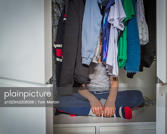 Boy hiding behind clothes in closet - p1023m2208308 by Tom Merton