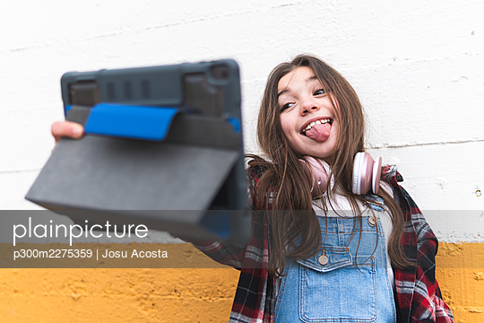 Cheerful girl sticking out tongue while taking selfie through digital tablet in front of wall - p300m2275359 by Josu Acosta