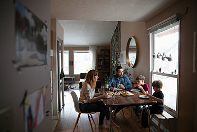 Family eating pizza at dining table - p1192m1567313 by Hero Images