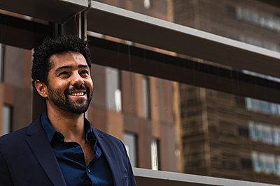 Confident entrepreneur smiling against building in city - p300m2227095 by NOVELLIMAGE