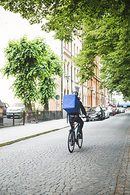 Rear view of food delivery man riding bicycle on street in city - p426m2145435 by Maskot
