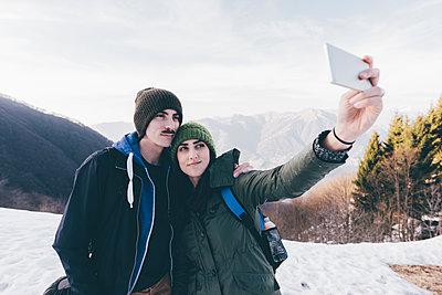 Hiking couple taking selfie in snowy mountains, Monte San Primo, Italy - p429m1448176 by Eugenio Marongiu