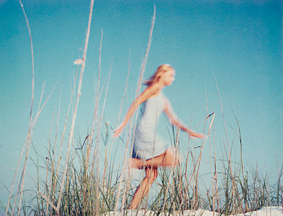 Young woman running through tall dune grass, side view - p675m922761 by Matthieu Spohn