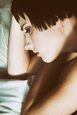 Sad young woman laying down in bed looking away  - p794m1508353 by Mohamad Itani