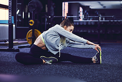 Side profile of young woman sitting and stretching on the floor at fitness centre - p1166m2095528 by Cavan Images