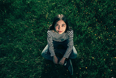 Smiling Caucasian teenage girl sitting in grass - p555m1531621 by Vladimir Serov