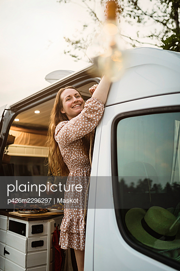 Smiling woman looking away while standing in motor home - p426m2296297 by Maskot