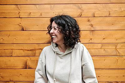 Smiling woman in front of wooden wall - p300m2282290 by Kiko Jimenez