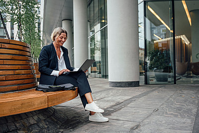 Smiling businesswoman using laptop while sitting on bench at office park - p300m2293910 by Vasily Pindyurin