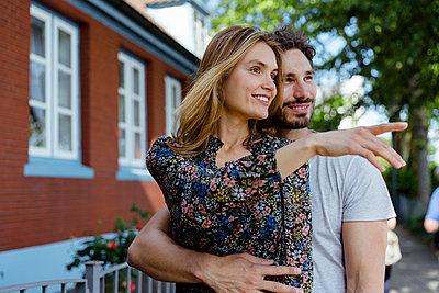 Paar steht glücklich vor Haus - p432m2093226 von mia takahara