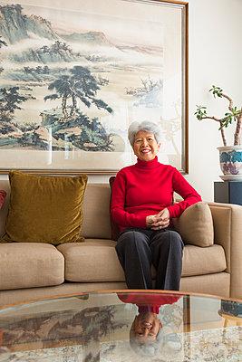 Chinese woman sitting on sofa - p555m1463669 by Don Mason
