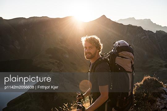Junger Mann genießt Blick auf Bergsee - p1142m2056638 von Runar Lind