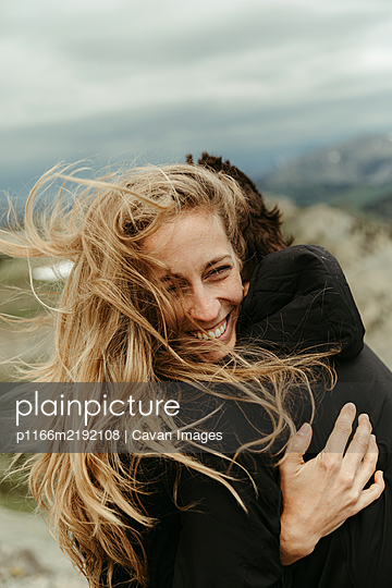 woman with wind swept long blonde hair laughs and hugs her partner - p1166m2192108 by Cavan Images