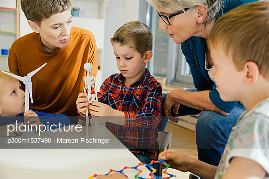 Children and pre-school teachers with wind turbine and anatomical model in kindergarten - p300m1537490 by Mareen Fischinger