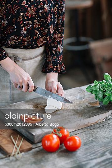 Woman preparing Caprese Salad, partial view - p300m2012395 von Alberto Bogo