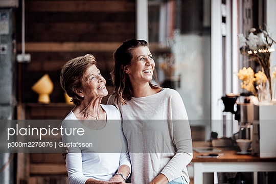 Happy young woman with grandmother looking away while standing at home - p300m2276876 by Gustafsson