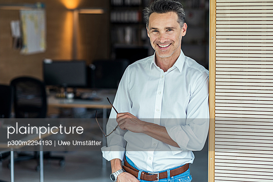 Smiling businessman with eyeglasses leaning on office doorway - p300m2294193 by Uwe Umstätter