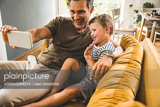 Father taking selfie with son through mobile phone at home - p300m2294216 by Uwe Umstätter