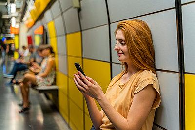 Woman using smartphone in underground station - p300m2139921 by VITTA GALLERY
