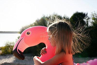 Girl hugging flamingo pool float - p300m2143646 by Ekaterina Yakunina