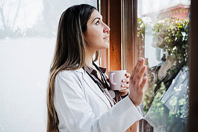 Thoughtful female doctor looking through window while having coffee - p300m2265048 by Eva Blanco