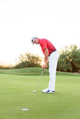 Hispanic golfer putting on golf course - p555m1472888 by Kolostock