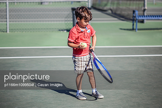 Boy (4-5) with tennis racket and ball