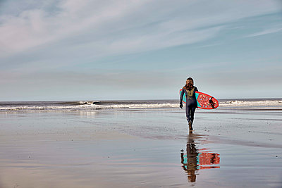 Man holding a surf board walking out to the sea at low tide.  - p1100m2010488 by Mint Images