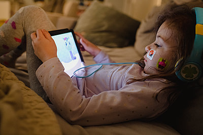 Young girl with bandage on face playing with tablet - p1166m2261694 by Cavan Images