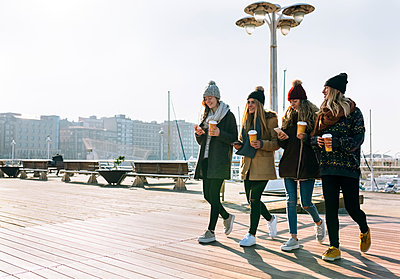 Four friends with coffee to go and cell phones walking on promenade in winter - p300m1228077 by Marco Govel