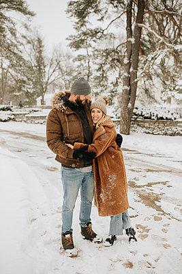 Canada, Ontario, Hugging couple standing on snowy road - p924m2271221 by Sara Monika