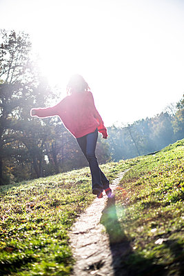 Young woman takes a walk in the park  - p975m2222101 by Hayden Verry