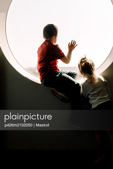 Siblings looking through window from hotel room - p426m2102050 by Maskot