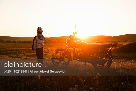 Rear view of boy and motorcycle at sunset, Sarsy village, Sverdlovsk Region, Russia - p429m1021994f by Aliyev Alexei Sergeevich