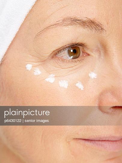 Frau mit Creme im Gesicht  - p6430122 von senior images