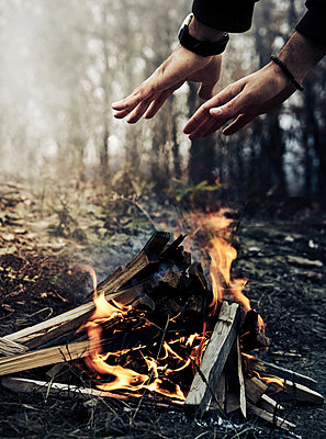 Cropped image of man warming hands over campfire in forest during winter - p1166m2105869 by Cavan Images