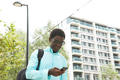 Smiling male entrepreneur using smart phone in city on sunny day - p300m2241575 by Pete Muller