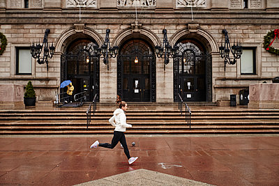 A female runner running through the city - p343m1173321 by Josh Campbell