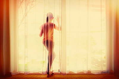 Mixed race girl behind curtain looking out window - p555m1413111 by Donald Iain Smith