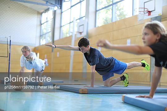 Sportive teenager making stretching exercise - p1258m1159792 von Peter Hamel