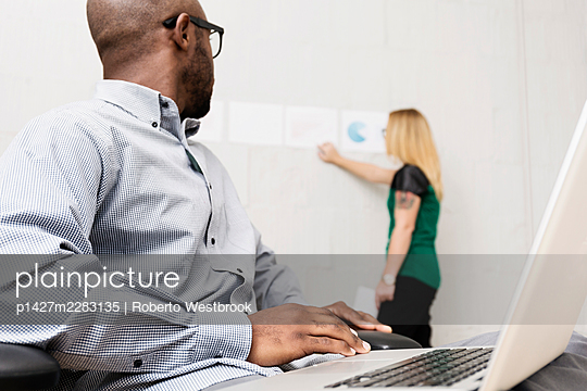 Young business partners working in design office - p1427m2283135 by Roberto Westbrook