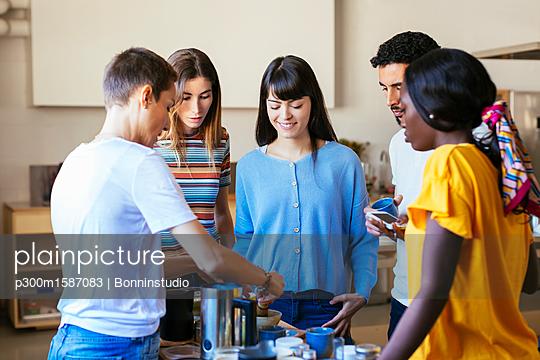 Friends and instructor in a cooking workshop preparing a drink - p300m1587083 von Bonninstudio