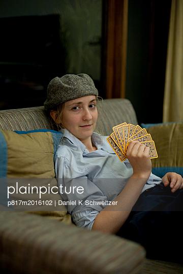 Junge Frau hält Kartenspiel - p817m2016102 von Daniel K Schweitzer