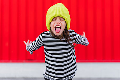 Portrait of little girl wearing striped shirt and yellow cap sticking out tongue in front of red background - p300m2102729 von Eloisa Ramos