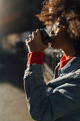 Close-up of afro young woman drinking coffee during sunny day - p300m2213913 by Boy photography