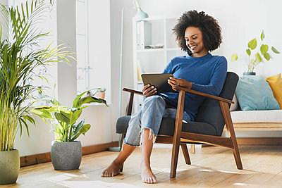 Young woman using digital tablet while sitting on armchair at home - p300m2277510 by Steve Brookland