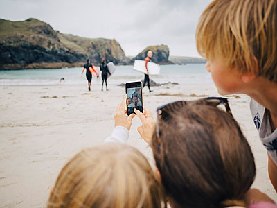 Woman taking selfie with kids from mobile phone at beach - p426m1543051 by Maskot