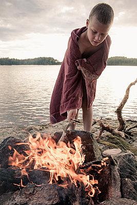 Boy wrapped in towel standing by bonfire at lake - p426m844555f by Katja Kircher